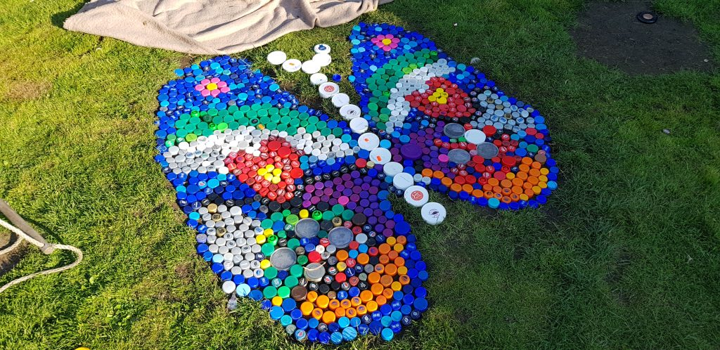 This beautiful upcycled art was created by the kids. The turned unwanted plastic bottle caps into this amazing garden craft.