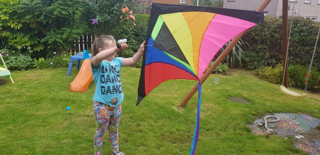 Holding a rainbow kite up after building it